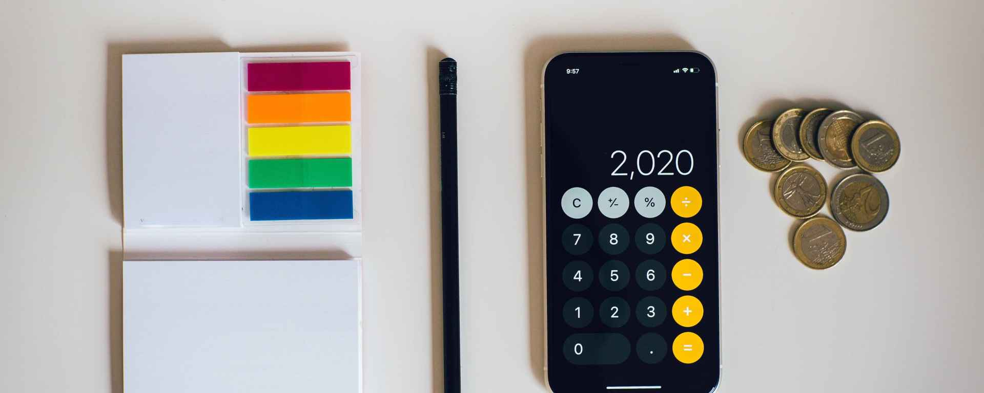 Picture of calculator, coins, notepad and pencil